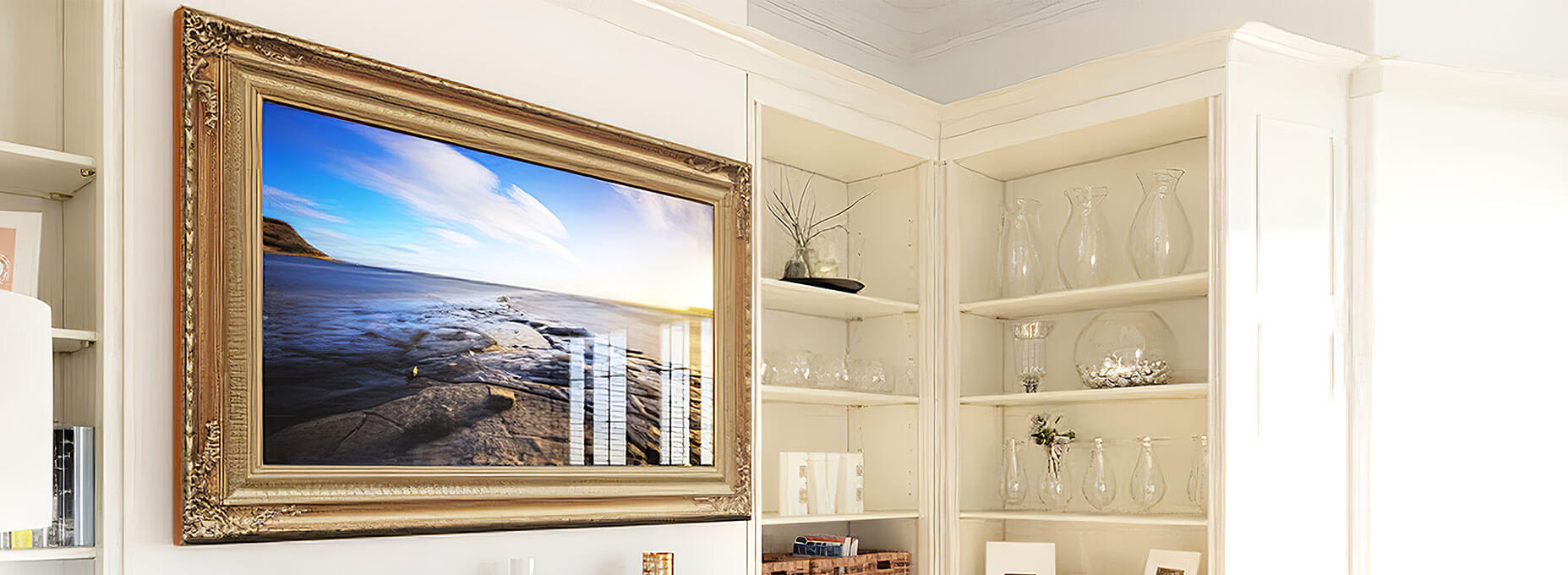 A smart TV framed in gold with classic and intricate designs on four corners attached to a wall in white room.